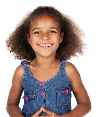 Schattige leuke Afrikaans kind met afro haar dragen van een denim jurk. Het meisje bevindt zich en lacht naar de camera.