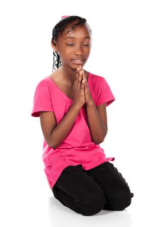 ni�o orando: Peque�o ni�o africano adorable con las trenzas con una camisa de color verde brillante y pantalones vaqueros flacos negros. La chica est� de rodillas y rezando. Foto de archivo