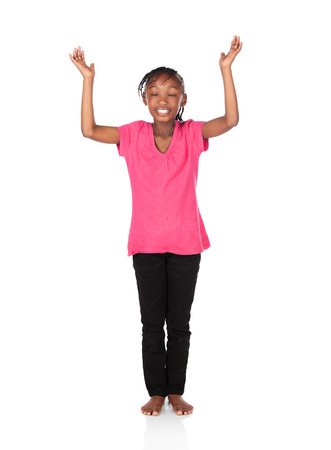 hands lifted up: Adorable small african child with braids wearing a bright green shirt and black skinny jeans. The girl is worshipping with her hands lifted up. Stock Photo