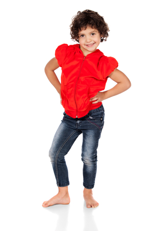 hooded top: Adorable small caucasian child with curly hair wearing a bright red hooded top and blue jeans. The girl is standing and smiling at the camera. Stock Photo