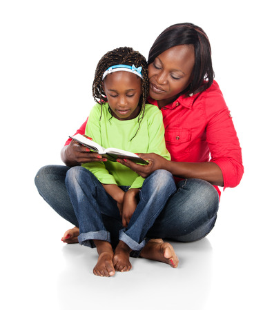 Adorable small african child with braids wearing a bright green shirt and blue jeans and her mother wearing a red shirt. The mom is reading to the girl from a book.