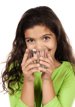 Pretty cute caucasian girl wearing a green long sleeve top. The girl is holding a clear glass of water. photo
