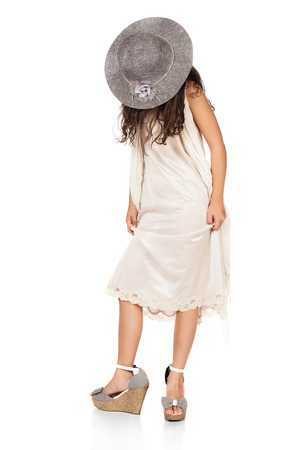Pretty cute caucasian girl is playing dress up. She is wearing a beige dress, grey hat and high heel shoes. photo