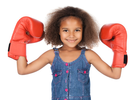 Adorable cute african child with afro hair wearing a denim dress. The girl is wearing big red boxing gloves.