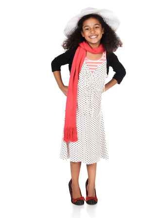 Adorable cute african child with afro hair is playing dress up. She is wearing a white dress with dots, a hat, scarf and high heel shoes.