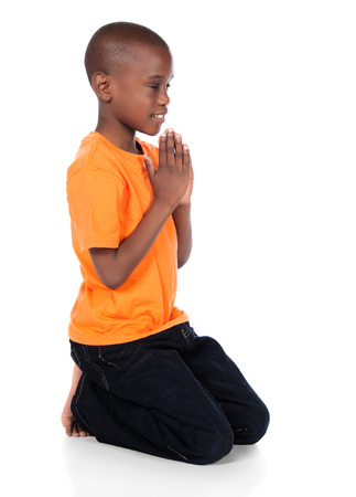 Cute african boy wearing a bright orange t-shirt and dark denim jeans. The boy is kneeling and praying.
