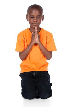 ni�o orando: Muchacho africano lindo que lleva un color naranja brillante t-shirt y jeans oscuros. El chico est� de rodillas y rezando.