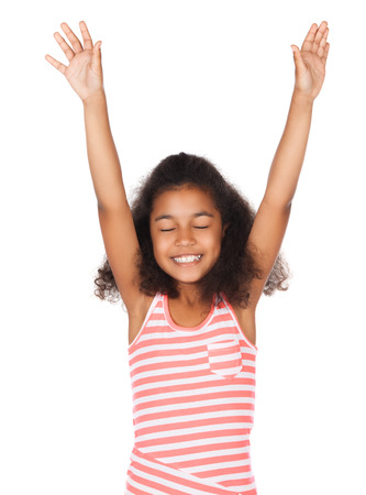 Adorable cute african child with afro hair wearing a white and pink striped dress. The girl is worshipping with her hands lifted up.