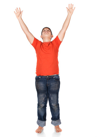 christian worship: Young caucasian boy wearing an orange t-shirt and blue jeans. The boy is worshipping with his hands lifted up.
