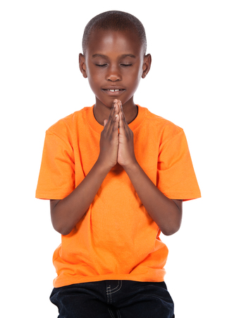 Cute african boy wearing a bright orange t-shirt and dark denim jeans. The boy is kneeling and praying. photo