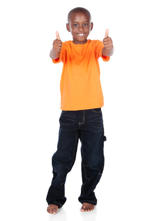 Cute african boy wearing a bright orange t-shirt and dark denim jeans. The boy is showing a thumbs up to the camera. Stock Photo