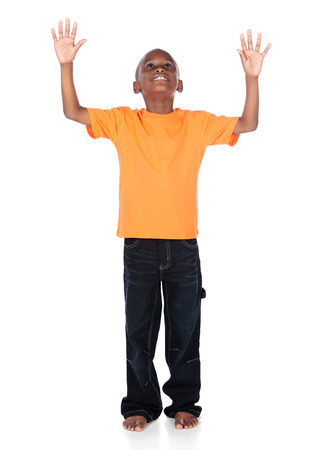 Cute african boy wearing a bright orange t-shirt and dark denim jeans. The boy is worshipping with his hands lifted up. photo