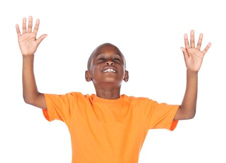 Leuke Afrikaanse jongen droeg een fel oranje t-shirt. De jongen is aanbidden met zijn handen opgeheven. Stockfoto
