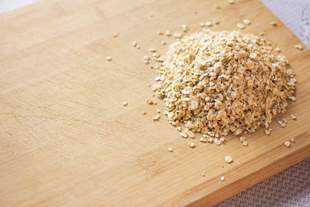 Heap of uncooked oats on a wooden chopping board. Image contains copy space. photo