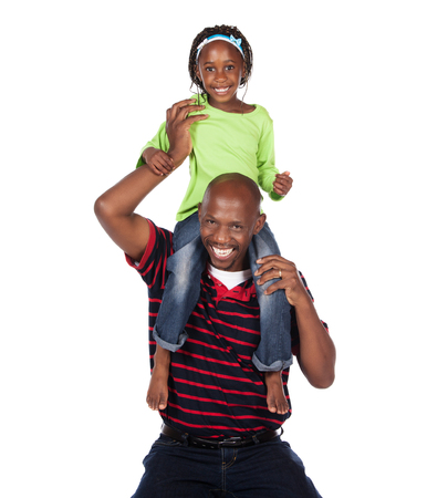 Adorable small african child with braids wearing a bright green shirt and blue jeans is playing with her father. He is wearing a red striped shirt. photo