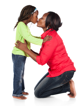 Adorable small african child with braids wearing a bright green shirt and blue jeans and her mother wearing a red shirt. The mom is kissing the girl. photo