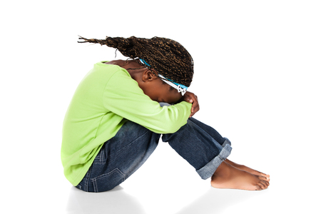bowed head: Adorable small african child with braids wearing a bright green shirt and blue jeans. The girl is sitting with her head bowed. Stock Photo