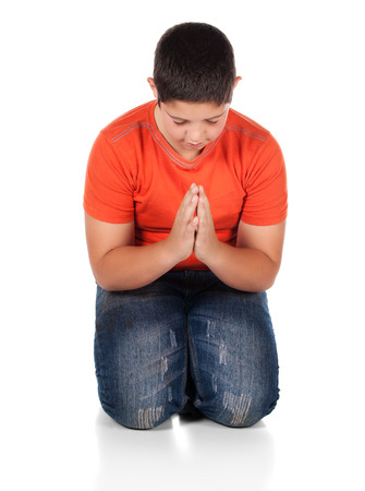 Young caucasian boy wearing an orange t-shirt and blue jeans. The boy is kneeling and praying. photo