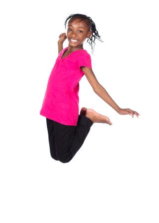 skinny jeans: Peque�o ni�o africano adorable con las trenzas con una camisa de color verde brillante y pantalones vaqueros flacos negros. La ni�a est� saltando y sonriendo. Foto de archivo