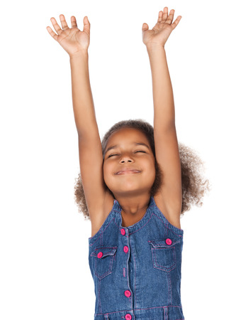 praise: Adorable cute african child with afro hair wearing a denim dress. The girl is worshipping with her hands lifted up.