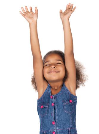 Adorable enfant africain mignon avec des cheveux afro portant une robe en jean. La jeune fille adore avec ses mains levées vers le haut.
