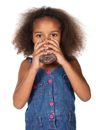 glass of water: Adorable cute african child with afro hair wearing a denim dress. The girl is drinking water from a clear glass.