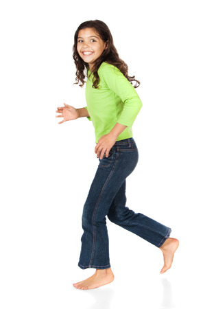 Pretty cute caucasian girl wearing a green long sleeve top and blue jeans is running and smiling at the camera.