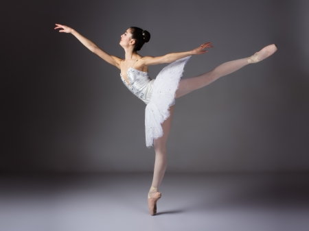 pointe shoes: Beautiful female ballet dancer on a grey background. Ballerina is wearing a white tutu and pointe shoes.