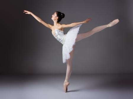 Mooie vrouwelijke balletdanser op een grijze achtergrond. Ballerina draagt een witte tutu en spitzen.