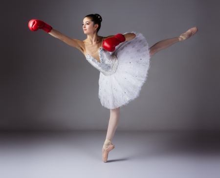 ballerina girl: Beautiful female ballet dancer on a grey background. Ballerina is wearing a white tutu and pointe shoes.