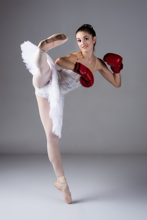Beautiful female ballet dancer on a grey background. Ballerina is wearing a white tutu, pointe shoes and red boxing gloves. photo