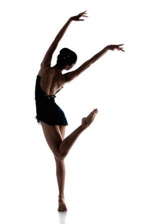 白い背景で隔離された美しい女性のバレエ ダンサーのシルエット。バレリーナは裸足と暗いレオタードと短いドレスを着てします。