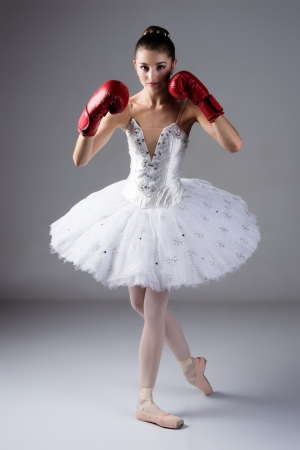 Beautiful female ballet dancer on a grey background. Ballerina is wearing a white tutu, pointe shoes and red boxing gloves.