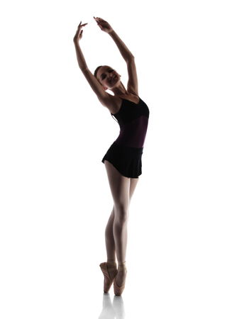 Silhouette of a beautiful female ballet dancer isolated on a white background. Ballerina is wearing a black leotard, pink stockings, pointe shoes and a black dress. photo