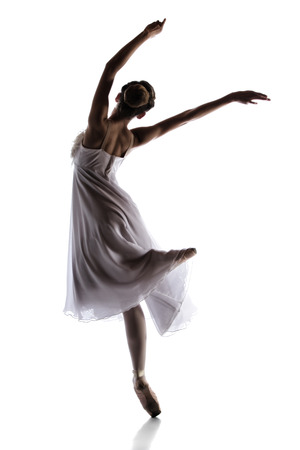 Silhouette of a beautiful female ballet dancer isolated on a white background. Ballerina is wearing a white dress with feathers and pointe shoes. Stock Photo