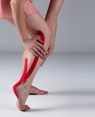 strapping: Red strapping on an injured calf of a young adult female dancer.