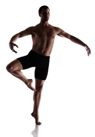 Silhouette of an muscular adult male modern contemporary ballet style dancer. Dancer is wearing black ski pants and is isolated on a white background. photo