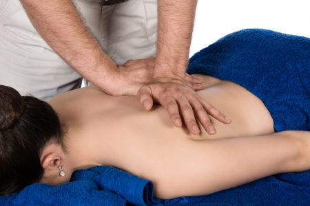 Adult male physiotherapist treating the back of a female patient. Patient is lying down on a bed and is covered with royal blue towels. photo