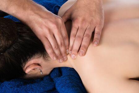 masaje deportivo: Macho adulto fisioterapeuta tratamiento de la espalda de un paciente. El paciente est� acostado en una cama y se cubri� con toallas azules reales.
