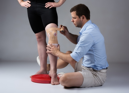 strapping: Adult male physiotherapist strapping the knee of a male patient. Stock Photo