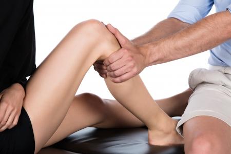 masaje deportivo: El macho adulto fisioterapeuta tratar el pie de un paciente femenino. El paciente est? sentado en una cama.