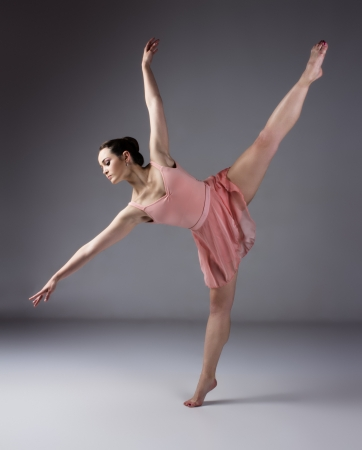 Beautiful female ballet dancer on a grey background. Ballerina is barefoot and wearing an orange dress and leotard. photo