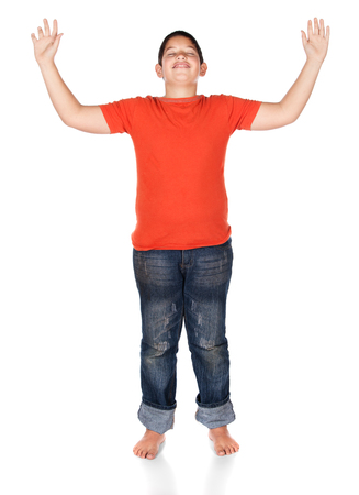 Young caucasian boy wearing an orange t-shirt and blue jeans. The boy is worshipping with his hands lifted up. photo