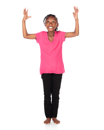 Adorable small african child with braids wearing a bright green shirt and black skinny jeans. The girl is worshipping with her hands lifted up. photo