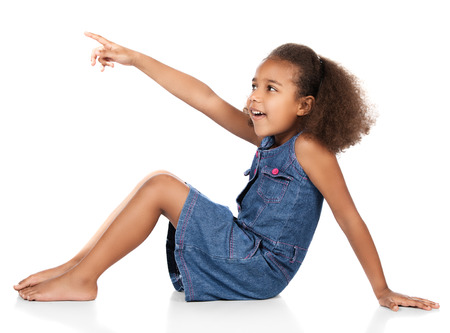 Adorable cute african child with afro hair wearing a denim dress. The girl is sitting and pointing away from the camera. photo