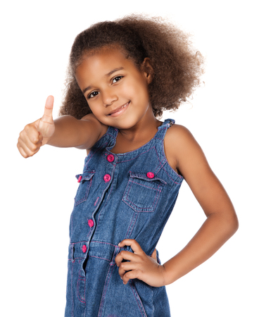 Adorable cute african child with afro hair wearing a denim dress. The girl is showing a thumbs up to the camera. photo