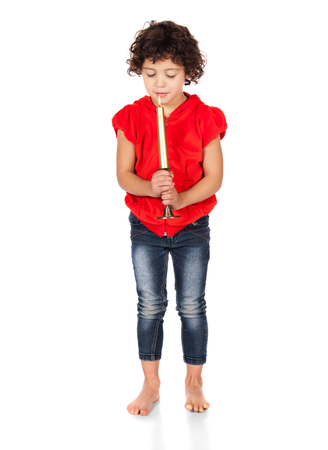 hooded top: Adorable small caucasian child with curly hair wearing a bright red hooded top and blue jeans. The girl is holding a candle. Stock Photo