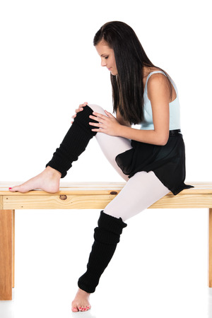 leg warmers: Beautiful female modern jazz contemporary style dancer isolated on a white background. Dancer is wearing a blue leotard, black skirt and leg warmers and is holding her injured knee.