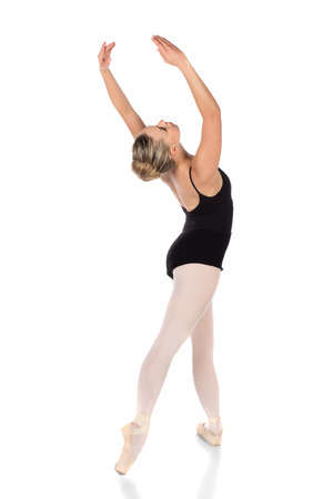 Beautiful young female classical ballet dancer on pointe shoes wearing a black leotard and pink stockings isolated on a white studio background