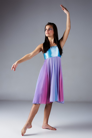 Beautiful female modern jazz contemporary style dancer on a grey background. Dancer is barefoot and wearing a blue and purple dress. photo